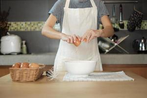 cozinheira de avental branco está quebrando um ovo na cozinha de casa. foto