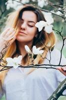 imagem borrada de menina bonita apreciando flores de magnólia, olhos fechados foto