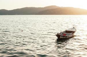 velho barco a remo de madeira na água ao pôr do sol foto