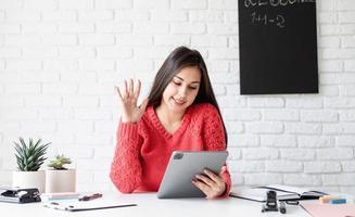 jovem mulher com fones de ouvido pretos ensinando inglês on-line usando um tablet foto