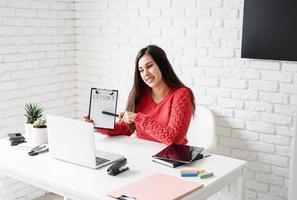 jovem latina de suéter vermelho ensinando inglês online foto