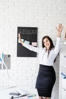 jovem professor de latim inglês com as mãos levantadas ensinando inglês online foto