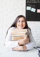 jovem professora sentada com uma pilha de livros olhando para longe, pronta para a aula foto