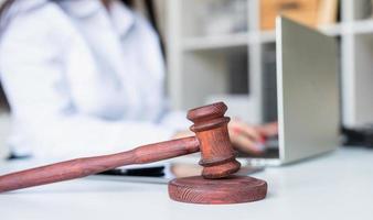 close-up do martelo de madeira, advogado trabalhando no laptop foto
