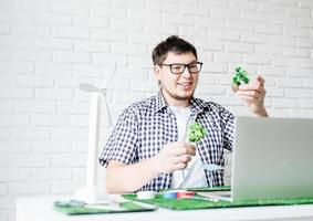 jovem fazendo projeto de energia renovável manequim conversando online foto