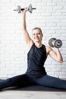 jovem mulher atlética malhando com halteres foto