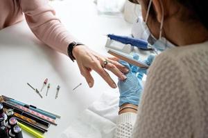 Mestre de manicure em luvas usando lixa de unha para polir a unha de uma cliente foto