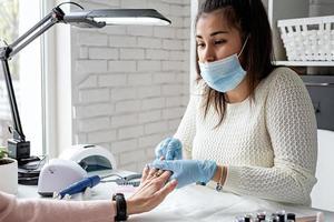 mestre de manicure limpando unhas fazendo manicure para uma cliente foto