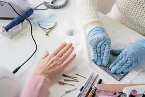 manicure mestre em máscara e luvas fazendo estamparia na cliente foto