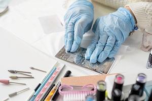 manicure mestre em máscara e luvas trabalhando com selos foto