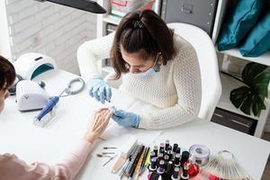 mestre de manicure usando pinças para fazer manicure para uma cliente foto