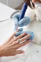 mestre de manicure usando uma máquina elétrica para polir as unhas foto