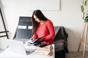 Uma mulher ensinando inglês online usando um laptop sentada no sofá foto