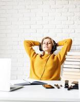 mulher na mesa relaxando com os olhos fechados após um longo estudo foto