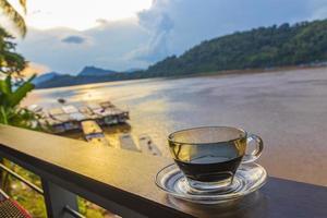 creme de café preto em copo transparente enquanto colorido pôr do sol laos. foto