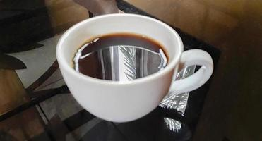 creme de café preto em copo branco na mesa preta laos. foto