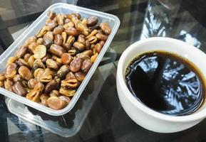 café preto xícara branca de favas na mesa preta laos. foto