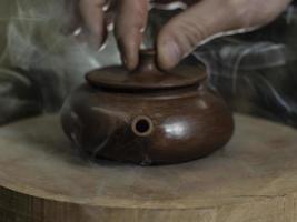 close-up de uma mão masculina fechando a tampa de um bule de barro feito de argila yixing foto