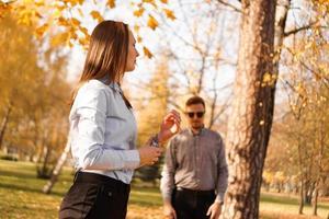homem desconhecido de óculos escuros observa uma mulher no parque foto