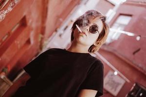 menina com cabelo ruivo curto e óculos de sol no espelho fumando cigarro foto