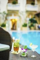 coquetéis estilosos em exótico bar tropical ao lado da piscina foto