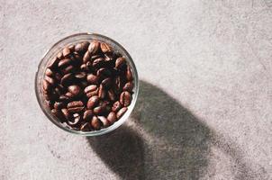 grãos de café frescos em uma tigela de vidro em um fundo foto