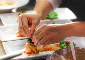 chef cozinhando, chef preparando comida, chef decorando prato na cozinha foto