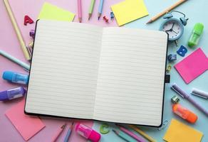 moldura de diferentes artigos de papelaria em fundo rosa e azul foto