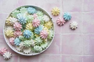 pequenos merengues coloridos na tigela de cerâmica foto