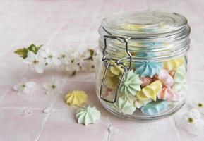 pequenos merengues coloridos na jarra de vidro foto