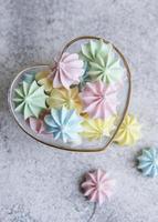 pequenos merengues coloridos na tigela em forma de coração foto