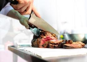 chef com faca e corte saboroso bife grelhado, chef na cozinha foto