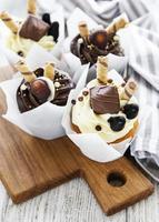 cupcakes de chocolate em uma tábua de madeira foto