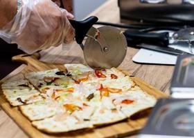 deliciosa pizza fresca, close-up do cortador de pizza na pizza italiana foto