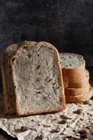 pão integral de grãos fatiados em fundo escuro de madeira rústico foto