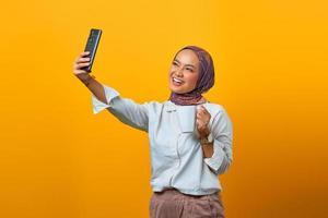 Mulher asiática alegre usando celular fazendo selfie enquanto segura a caneca foto