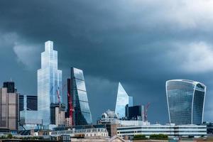 arranha-céus brilhantes do distrito financeiro da cidade de londres contra o céu tempestuoso. foto