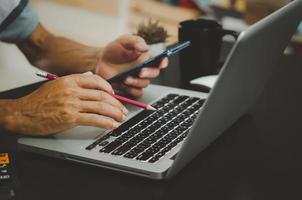 mão segurando um lápis, calculadora e telefone celular, computador foto
