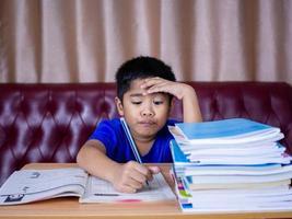 rapaz fazendo lição de casa e lendo sobre uma mesa de madeira. foto