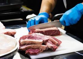 chef corta carne crua com uma faca em uma tábua, cozinheiro corta carne crua foto