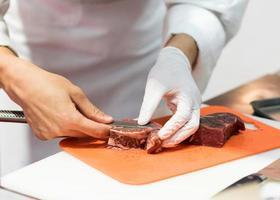chef cortando carne crua fresca com faca na cozinha foto