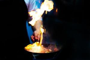 chef cozinhando com fogo em uma frigideira no fogão de cozinha foto