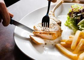 bife de porco com salada e batata frita foto