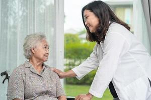 médico asiático ajuda paciente idosa asiática no hospital. foto
