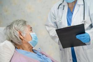 médico ajuda paciente sênior asiático usando máscara para proteger o coronavírus. foto