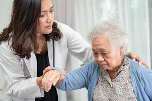 ajuda e cuidados, paciente idosa asiática sentada na cadeira de rodas foto