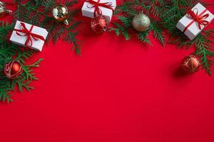 caixas de presente e decoração festiva. composição de Natal em fundo vermelho. foto