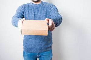 jovem anônimo com jeans entregando uma caixa de papelão foto