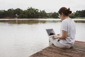 mulher adulta usando computador para trabalhar remotamente na margem do rio foto
