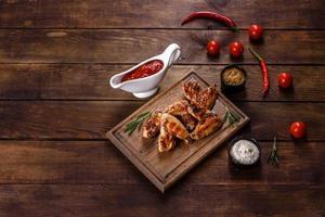 asas de frango picantes grelhadas em um fundo escuro com especiarias e ervas foto